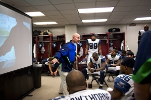 In the locker room at halftime, defensive coordinator Gus Bradley gives instructions to his players.