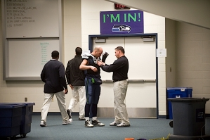 In the Seahawks locker room before the game, quarterback Matt Hasselbeck gets his pads adjusted by assistant coach Pat McPherson.