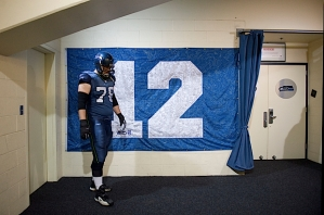 Offensive lineman Tyler Polumbus waits outside of the team's locker room next to a 12th Man flag signed by fans.