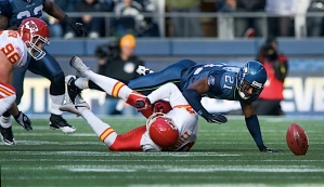 Seattle's Kelly Jennings dives over Kansas City holder Dustin Colquitt to recover the blocked field goal.