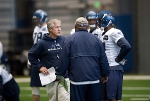 Head coach Pete Carroll talks with receivers coach Kippy Brown and receiver Ben Obomanu.