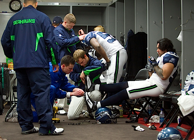 Members of the Seahawks equipment staff make last-minute changes to Lofa Tatupu's cleats in the locker room before the game.