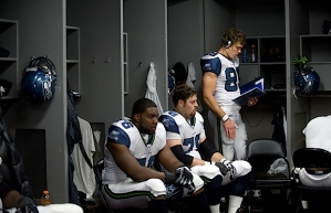 Tight end John Carlson (standing) goes over the game plan as Russell Okung and Tyler Polumbus wait to take the field.
