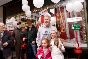 Seahawks head coach Pete Carroll poses with some young fans while he was bell-ringing on behalf of the Salvation Army in downtown Seattle during the lunch hour.