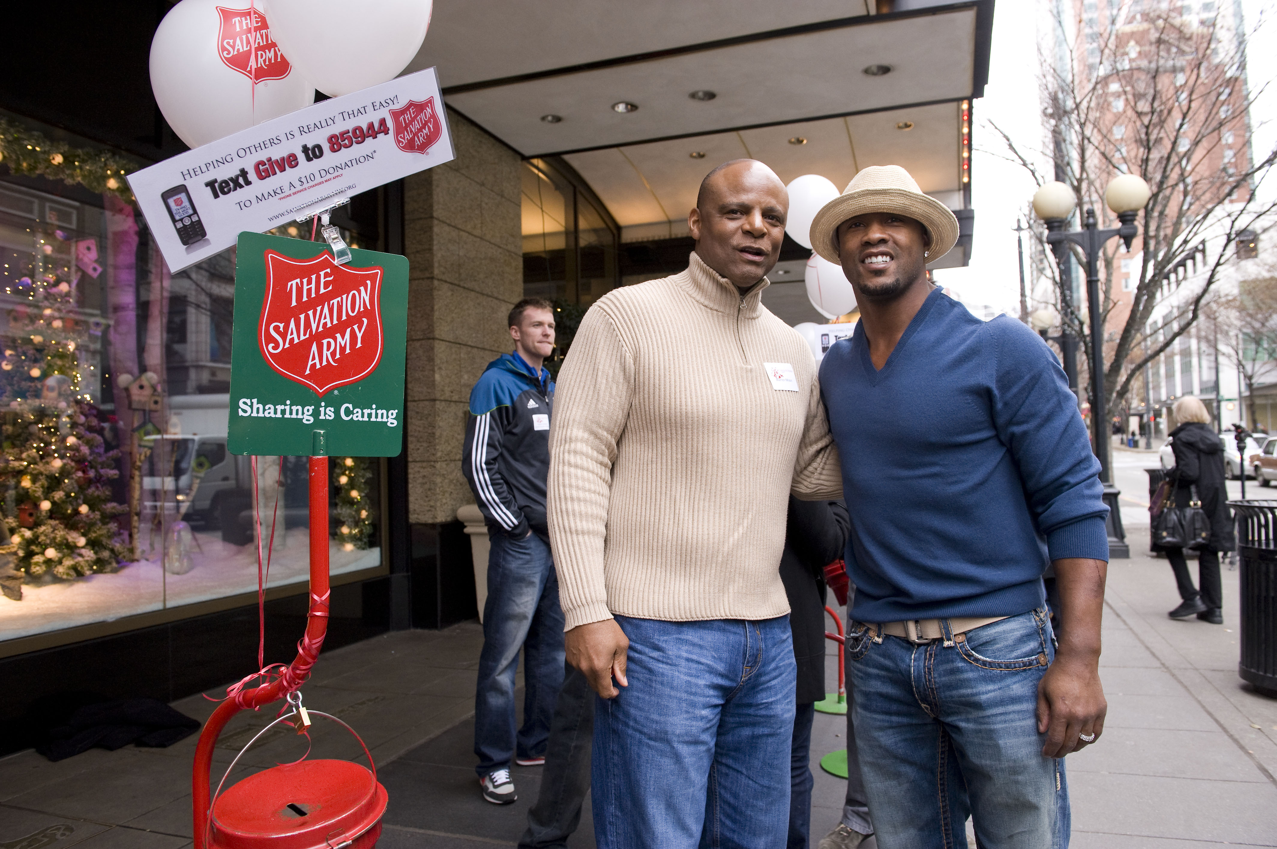 Seahawks broadcaster and former quarterback Warren Moon and current safety Lawyer Milloy pose outside of the downtown Nordstrom where they were bellringing for the Salvation Army during the lunch hour.