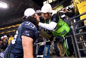 Defensive tackle Craig Terrill, wearing a hat proclaiming the Seahawks as NFC West Champions, runs over to the stands to give his wife Rachel a kiss before heading to the locker room.