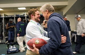 General manager John Schneider and head coach Pete Carroll, who made 270 personnel moves since taking over, congratulate each other in the locker room after winning the division title.