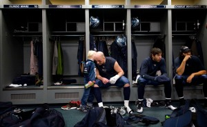 Hasselbeck shares a private moment with his son Henry after the postgame commotion had died down. At right are quarterbacks J.P. Losman and Charlie Whitehurst.