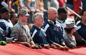Head coach Pete Carroll, his coaches and players joined with members of the armed forces to hold the American flag during the National Anthem.