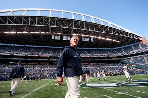 Head coach Pete Carroll strolls on the field under bright sunny skies before the game. However, two heavy squalls showered the field with rain during the first half.