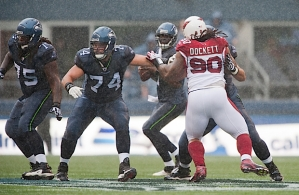 As heavy rains drenched CenturyLink Field, offensive linemen James Carpenter, John Moffitt and Max Unger (blocking Arizona's Darnell Dockett) fought to protect quarterback Tarvaris Jackson.