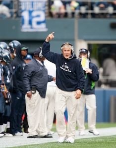 Head coach Pete Carroll winds up the 12thMan during the first half.