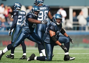 Seattle's Red Bryant celebrates a tackle for loss with teammate Clinton McDonald.