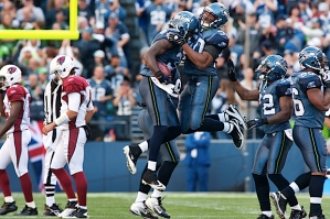 Sehawks defenders including K.J. Wright (leaping) celebrate Kam Chancellor's late interception that killed a Arizona drive in Seahawks territory and helped seal the victory..