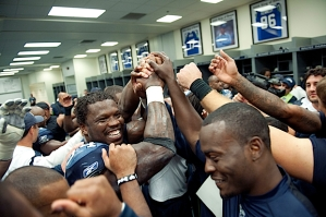 The Seahawks gather together in their locker room after head coach Pete Carroll's post game comments.