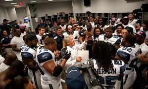In the locker room, happy players, coaches and staff members celebrates as head coach Pete Carroll addressed the team.