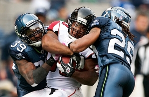 Defensive backs Brandon Browner (39) and Earl Thomas(29) sandwich Atlanta's Michael Turner.