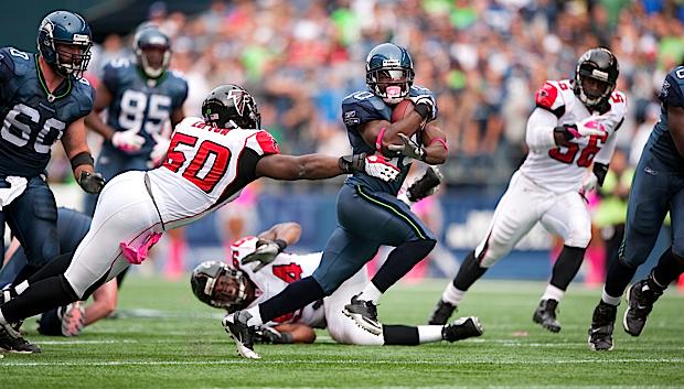 Running back Justin Forsett slides by Atlanta defender Curtis Lofton during the second quarter.