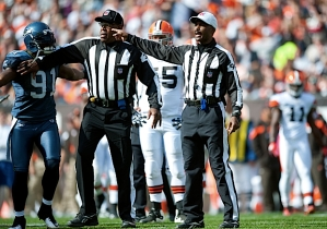 Head referee Mike Carey announces the penalty against Chancellor as Seattle's Chris Clemons seeks an explanation.