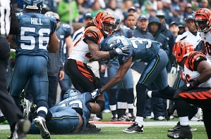 Cincinnati's Bernard Scott is tackled low by Seattle's Brandon Mebane and hit high by Brandon Browner.