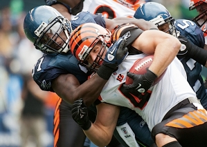 Seahawks defender Chris Clemons brings down Cincinnati's Brian Leonard.