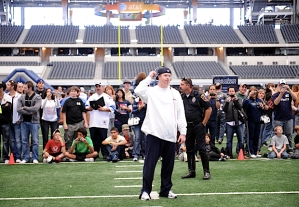 On three day road trips, the team does a brief walkthru practice at a local school then visits the stadium for a quick look at the surroundings. Making this trip unusual was Cowboys Stadium was full of fans as part of enhanced tour. Punter Jon Ryan is protected by security as he takes in sight lines from the hashmarks.