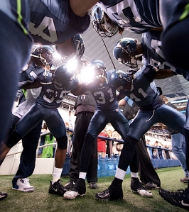 Game day arrives and under the roof of Cowboys Stadium, Seahawks defensive backs huddle before pregame warmups.