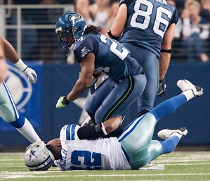 Seattle running back Marshawn Lynch doled out early punishment and knocked off the helmet of Cowboys safety Barry Church on a first half run.