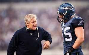 Head coach Pete Carroll congratulates Heath Farwell after a special teams tackle.