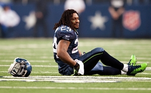 Marshawn Lynch sits on the turf after being tackled and losing his helmet.