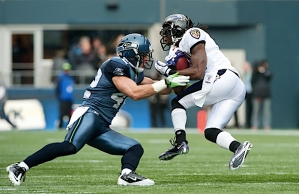 Cornerback Chris Maragos upends Baltimore's Ladarius Webb on a punt return in the first quarter of a hard-hitting game.