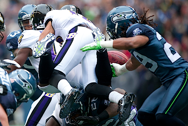 Baltimore's David Reed is hit hard on a kickoff return and the ball squirts loose, one of his two fumbles recovered by the Seahawks.