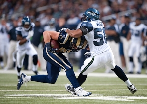 Linebacker K.J. Wright corrals Rams tight end Stephen Spach in the first half.