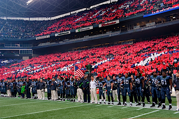 As the teams stood for the Star Spangled Banner, fans throughout the stadium joined to perform a card stunt that thanked America's service veterans.