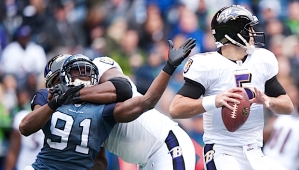 Seahawks defensive end Chris Clemons is collared as he tries to get to Baltimore quarterback Joe Flacco.