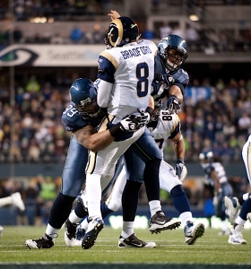 Defensive lineman Alan Branch and linebacker K.J. Wright combine to put a vicious hit on St. Louis quarterback Sam Bradford.