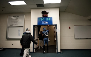"""Customarily one of the last players to leave the locker room, Marshawn Lynch """"taps in"""" as head coach Pete Carroll follows."""
