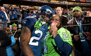 "Marshawn Lynch greets his mom on the sidelines during pregame. When asked about the Skittles habit after the game, Lynch replied, ""you should ask my Mama""."