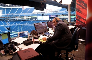 Monday Night Football play-by-play man Mike Tirico reviews his notes in the booth long before the stands at CenturyLink Field were filled with members of the 12thMAN.